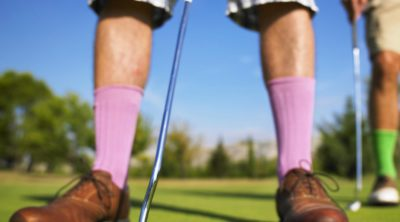 man in golf shoes putting