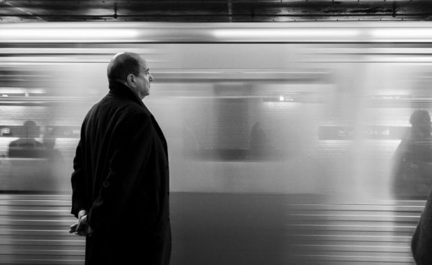 balding man at a train station thinking about hair restoration for men