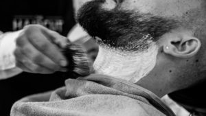 client getting a beard trim at a barbershop for men
